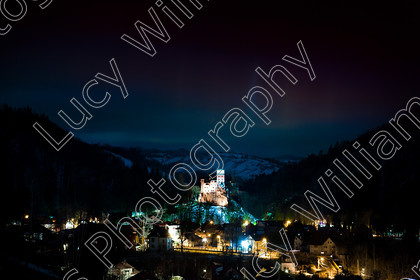 castel bran   A night view over Bran with an illuminated Bran Castle in the distance   Keywords: architecture, Transylvania, building, eastern, europe, famous, historic, history, old, romania, colour, horizontal, Bran Castle, Castell Bran, Törzburg, Törcsvár, national monument, Dracula's Castle, fortress, Queen Marie, night, street light