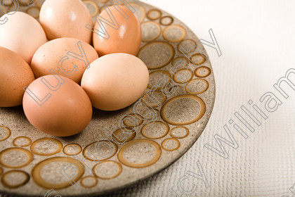 eggs   Seven eggs on an unusual brown plate with circle pattern   Keywords: eggs, raw, hard boiled, healthy, dairy, food, circles, brown, colour, horizontal