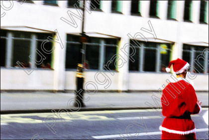 blurry santa   Santa running along a London Street to catch up with other Santas who have gathered together to celebrate London Santacon.   Keywords: Santa, Father Xmas, Father Christmas, carol singing, crowd, festive, jolly, fun, running, blurry, movement, santacon, santa convention, flash mob, pub crawl, red suit, white beard, people, London, street, Britain, UK, horizontal, colour, color