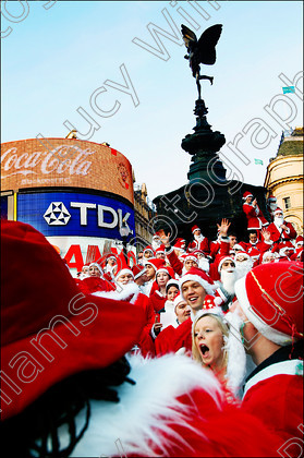 santapiccadilly   Santas gather to sing carols at Piccadilly Circus, London as part of the celebrations for London Santacon.   Keywords: Santa, Father Xmas, Father Christmas, Xmas, Christmas, carol singing, crowd, festive, jolly, fun, santacon, santa convention, flash mob, pub crawl, red suit, white beard, people, London, landmark, Piccadilly Circus, Eros, neon signs, blue sky, Britain, UK, vertical, colour, color